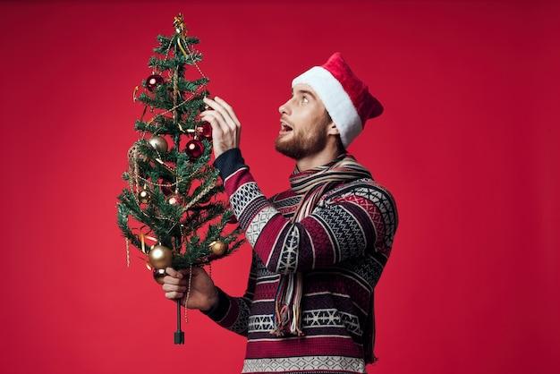 Homem com árvore de natal nas mãos brinquedos decoração feriado ano novo