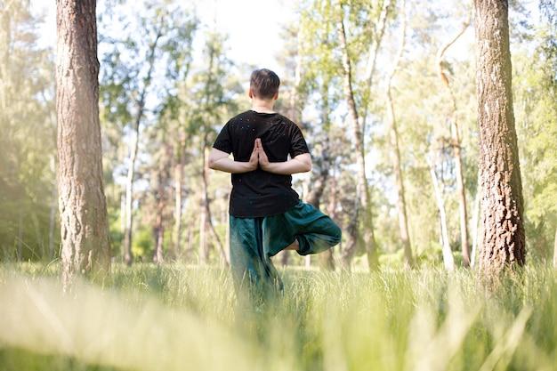 Homem com as mãos atrás das costas praticando ioga na natureza entre as árvores