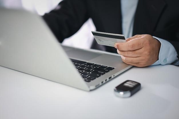 Homem com as mãos de terno preto sentado, segurando um cartão de crédito e usando o smartphone na mesa