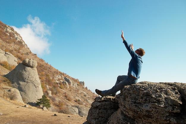 Homem com as mãos levantadas na rocha nas montanhas