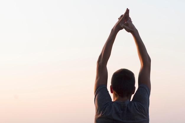Homem com as mãos no ar olhando para o céu