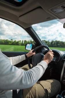 Homem com as mãos no volante, dia ensolarado e nublado, cópia espaço