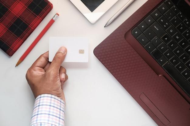 Homem com as mãos segurando um cartão de crédito e usando o teclado para fazer compras online