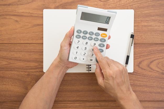 Homem com as mãos segurando uma calculadora com fundo de madeira