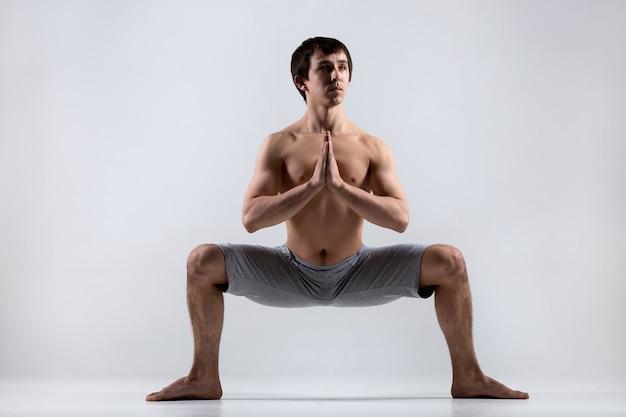 Homem com as pernas abertas e as mãos dobradas