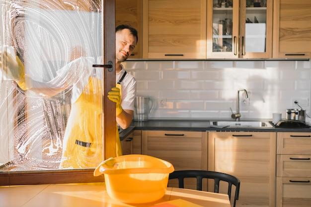 Homem com avental para limpar a janela