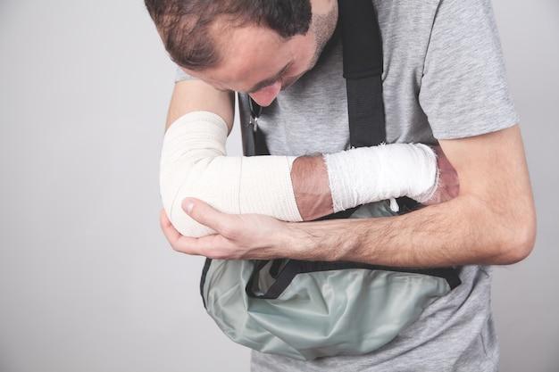 Homem com bandagem elástica no cotovelo.