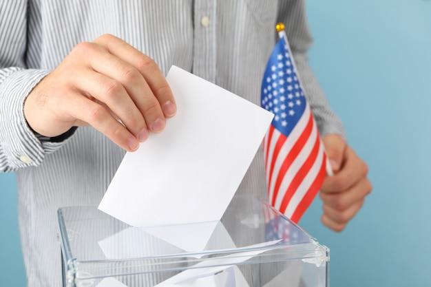 Homem com bandeira americana colocando a cédula na urna