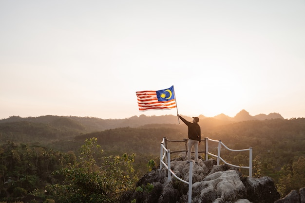 Homem com bandeira da malásia da malásia no topo da montanha