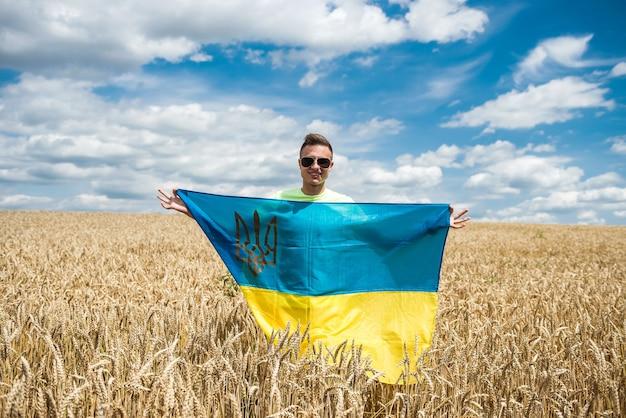 Homem com bandeira ucraniana no campo de trigo no verão. estilo de vida