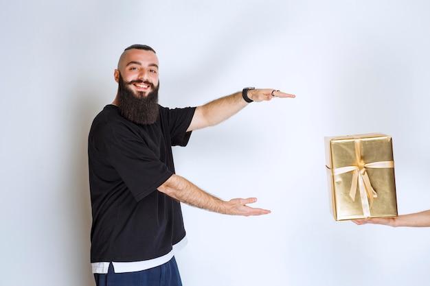 Homem com barba ansiando por levar uma caixa de presente dourada que lhe foi oferecida.