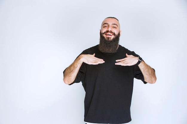 Homem com barba apontando para si mesmo.
