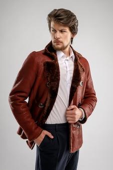 Homem com barba bonito brutal com barba e bigode no casaco de pele de carneiro com gola de pele