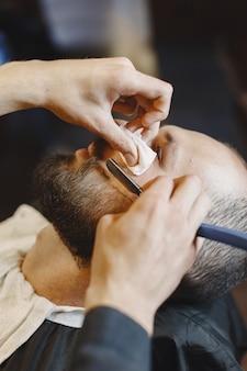 Homem com barba. cabeleireiro com um cliente. homem barbeado.