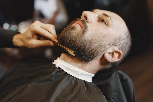 Homem com barba. cabeleireiro com um cliente. homem com pente e tesoura