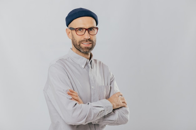 Homem com barba com aparência agradável mantém as mãos cruzadas, usa chapéu estiloso, óculos ópticos