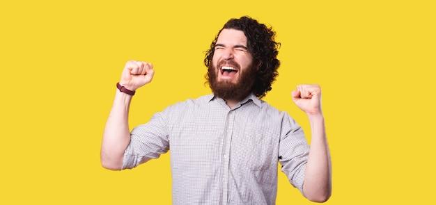 Homem com barba comemorando a vitória com os punhos erguidos e gritando sobre fundo amarelo