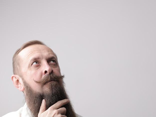Homem com barba comprida e bigode parado em frente a uma parede cinza