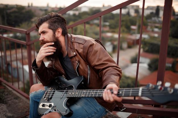 Homem com barba comprida e cabelos grisalhos, usa uma jaqueta de couro marrom com uma guitarra elétrica na mão e se senta perto da escada, tendo como pano de fundo uma garagem