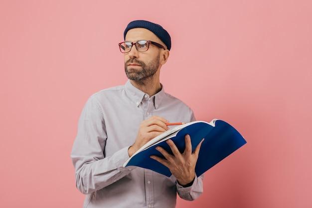 Homem com barba, concentrado de lado, pensa no que escrever
