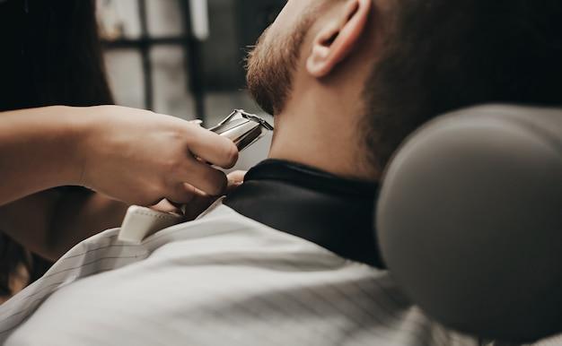 Homem com barba corta o cabelo com máquina elétrica em uma barbearia