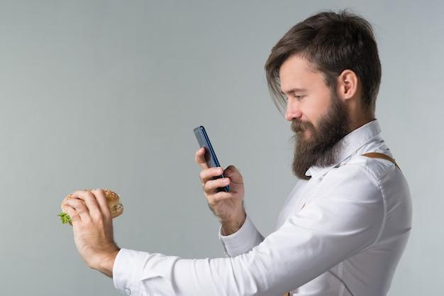 Homem com barba de camisa branca e suspensórios comendo junk food de um hambúrguer de fast food ou cheeseburguer e fotografa comida no smartphone em fundo cinza
