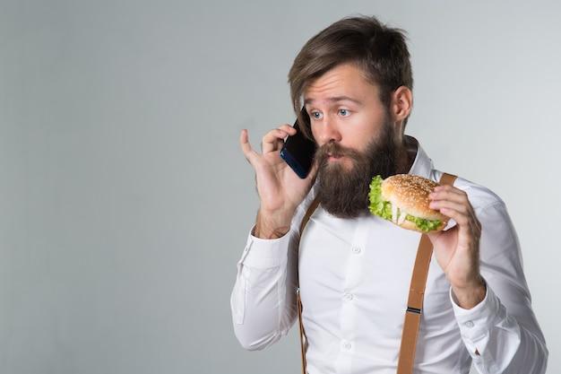 Homem com barba de camisa branca e suspensórios comendo junk food de um hambúrguer ou cheeseburguer de fast food e falando ao telefone em um fundo cinza