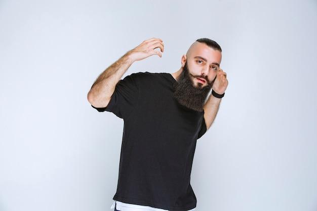 Homem com barba demonstrando os músculos do braço e se sentindo poderoso.