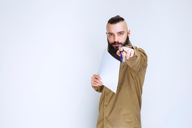 Homem com barba demonstrando seu projeto e esperando comentários.