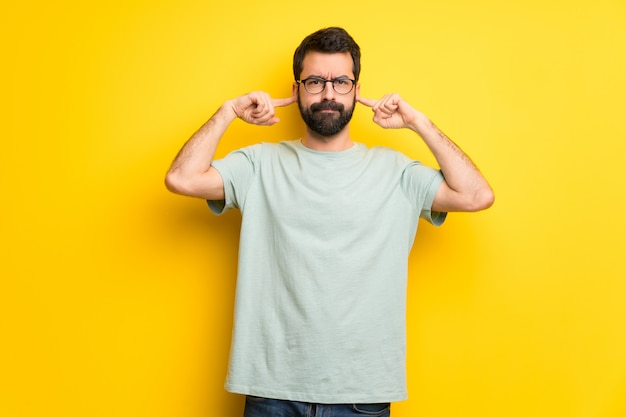 Homem, com, barba, e, camisa verde, cobertura, ambos, orelhas, com, mãos