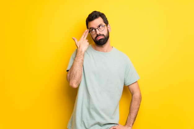 Homem com barba e camisa verde com problemas fazendo gesto de suicídio