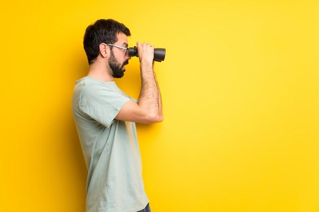 Homem com barba e camisa verde e olhando à distância com binóculos