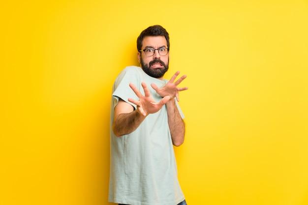 Homem com barba e camisa verde é um pouco nervoso e assustado esticando as mãos para a frente