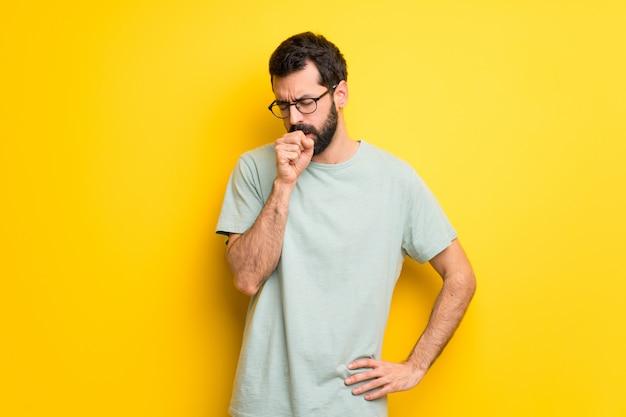 Homem com barba e camisa verde está sofrendo com tosse e se sentindo mal