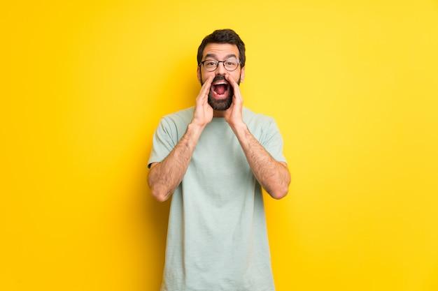 Homem com barba e camisa verde gritando e anunciando algo