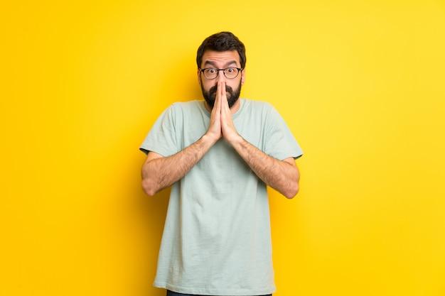 Homem com barba e camisa verde mantém a palma juntos. pessoa pede algo