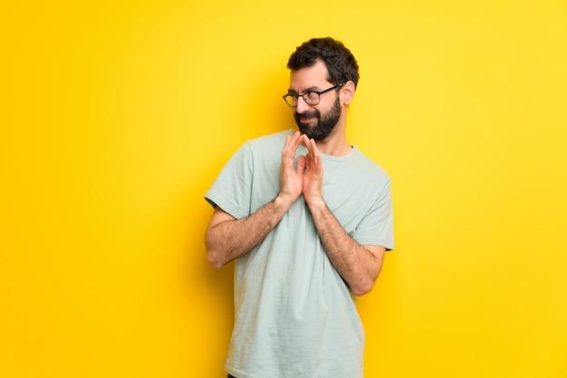 Homem com barba e camisa verde planejando algo