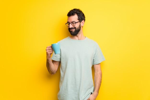 Homem com barba e camisa verde, segurando uma xícara de café quente