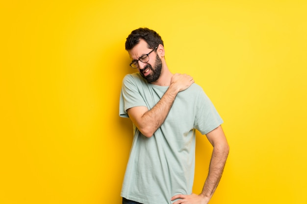 Homem com barba e camisa verde, sofrendo de dor no ombro por ter feito um esforço
