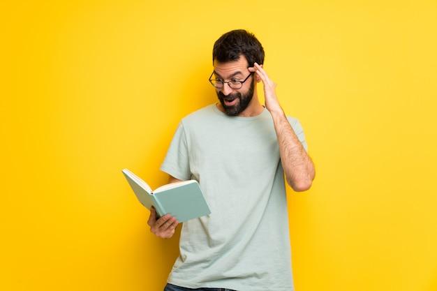 Homem com barba e camisa verde surpreso enquanto desfruta de ler um livro