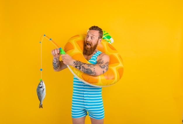 Homem com barba e donut inflável pega peixe