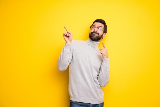 Homem com barba e gola alta apontando com o dedo indicador e olhando para cima