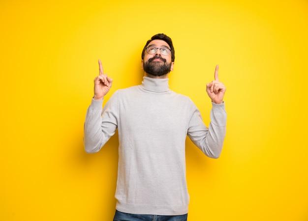Homem com barba e gola alta apontando com o dedo indicador uma ótima idéia
