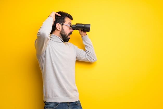Homem com barba e gola alta e olhando ao longe com binóculos