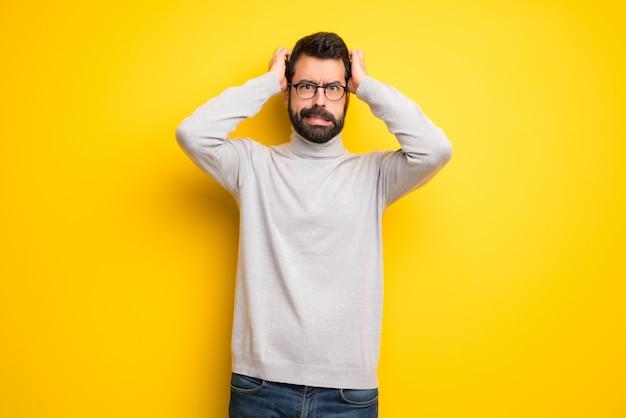 Homem com barba e gola alta leva as mãos na cabeça porque tem enxaqueca
