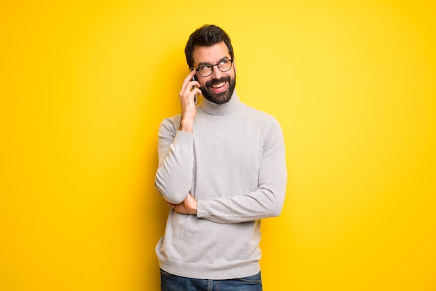 Homem com barba e gola alta, mantendo uma conversa com o telefone móvel