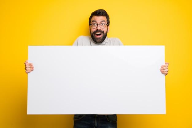 Homem com barba e gola alta segurando um cartaz para inserir um conceito