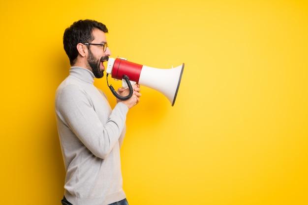 Homem com barba e gola gritando através de um megafone para anunciar algo em posição lateral