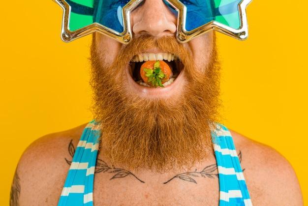 Homem com barba e óculos de sol comendo morango