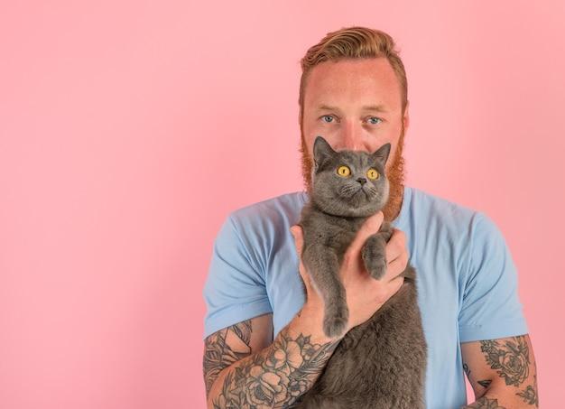 Homem com barba e tatuagens acariciando um gato cinza